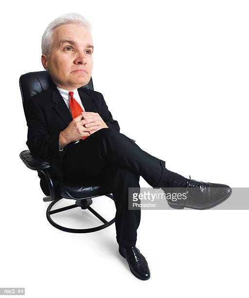 an adult male caucasian business executive in a dark suit sits back in his chair as he thinks