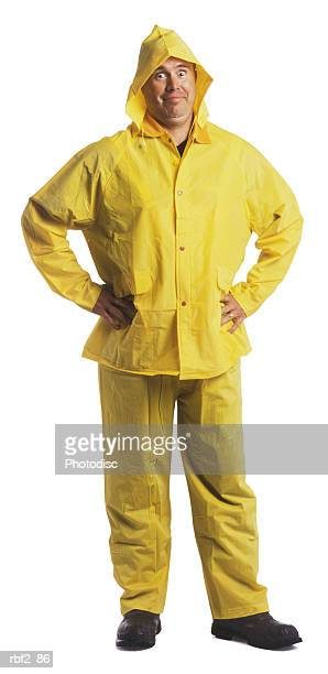 an adult male in a yellow rain gear puts his hands on his hips and smiles