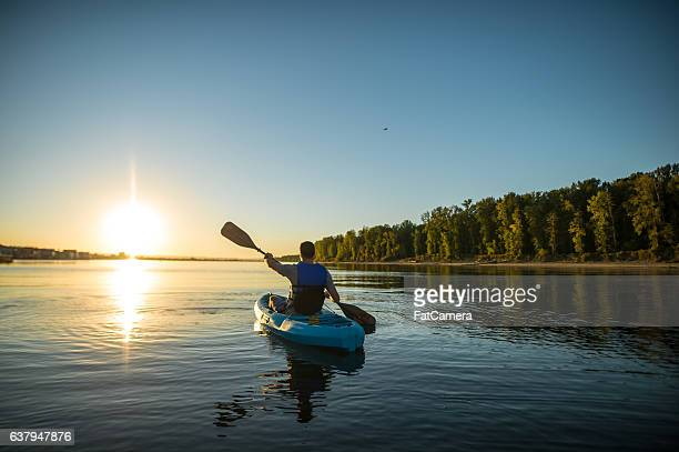 An adult male is kayaking at sunset on a peaceful