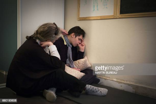 An adult takes care of JeanPhilippe a 18yearold autistic boy on March 24 2017 in Courbevoie northwest of Paris at the Lud'Eveil center for children...