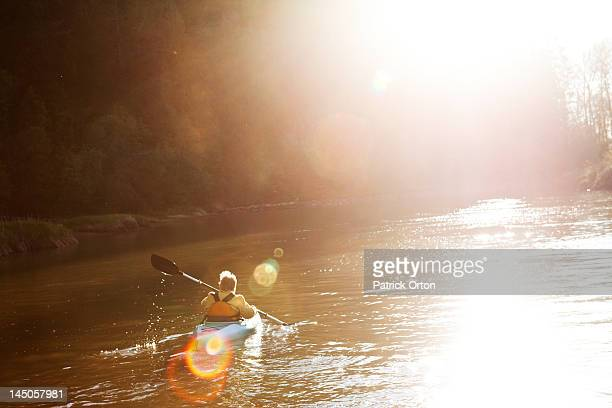 An adventurous retired women kayaking down a large river at sunset in Idaho.