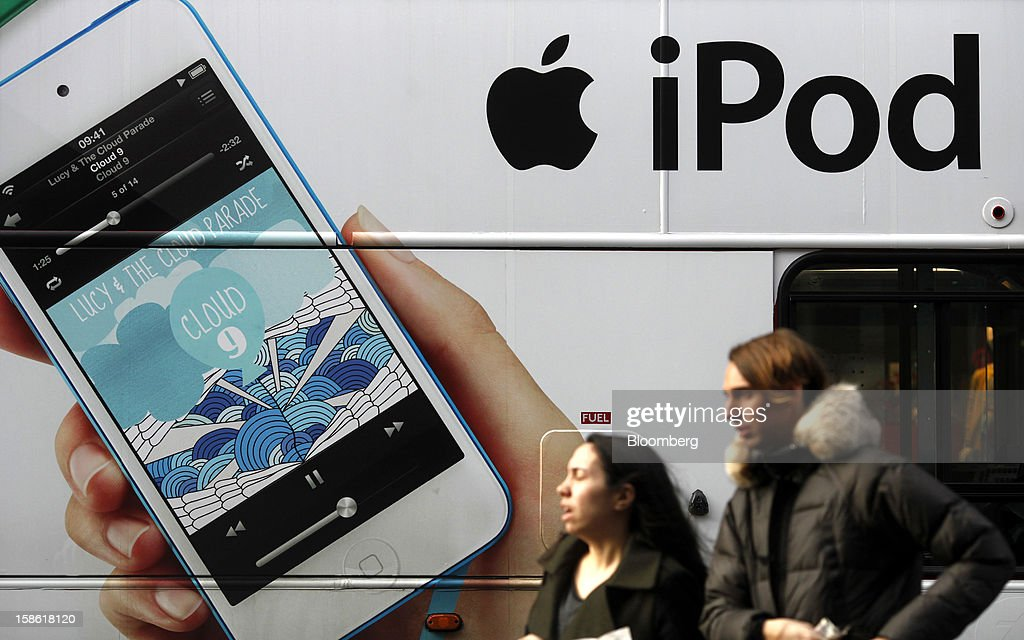 An advertisement for an Apple Inc. iPod is displayed on the side of a London bus in London, U.K., on Friday, Dec. 21, 2012. Britain's economy expanded less than previously estimated in the third quarter and the budget deficit unexpectedly widened in November, complicating Prime Minister David Cameron's attempts to bolster the recovery. Photographer: Simon Dawson/Bloomberg via Getty Images