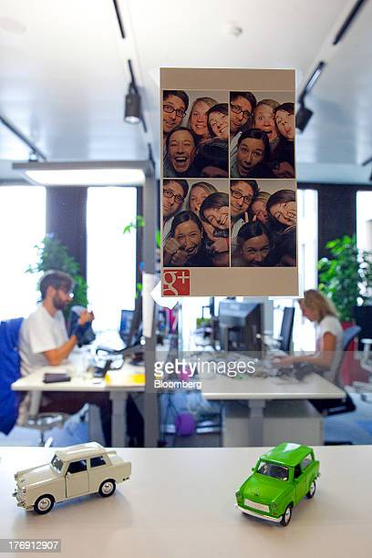 An advertisement for Google Inc's Google Plus social networking product sits on a window above model Trabant automobiles inside the company's offices...