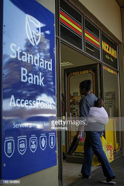 An advertisement for MPesa mobile phone money transfer services operated by Standard Bank Group Ltd sits on display outside a supermarket in Tembisa...