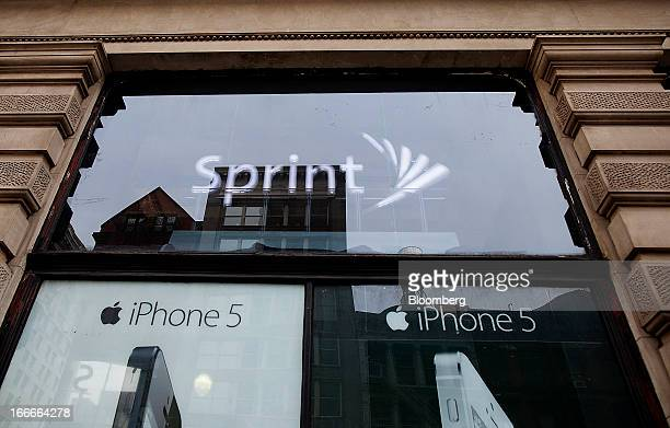 An advertisement for the Apple Inc iPhone 5 is displayed in the window of a Sprint Nextel Corp store in New York US on Monday April 15 2013 Dish...
