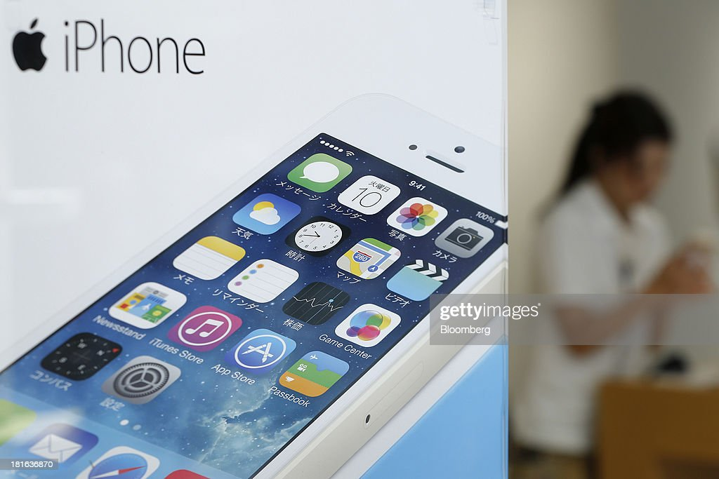 An advertisement for the Apple Inc. iPhone 5s is displayed while an employee prepares a headset for customers in the background at an NTT Docomo Inc. store in Tokyo, Japan, on Friday, Sept. 20, 2013. Apple Inc. attracted long lines of consumers at its retail stores today for the debut of its latest iPhones, in the company's biggest move this year to stoke new growth. Photographer: Kiyoshi Ota/Bloomberg via Getty Images