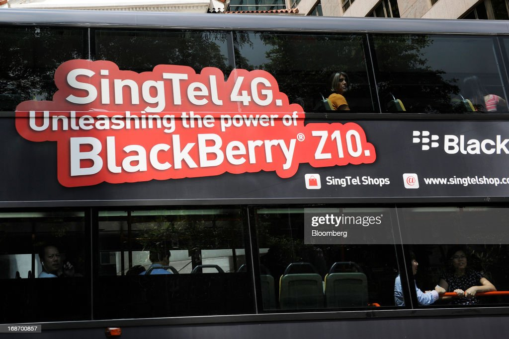 An advertisement for the BlackBerry Z10 smartphone on Singapore Telecommunications Ltd.'s (SingTel) 4G network is displayed on the side of a bus as it drives past in Singapore, on Tuesday, May 14, 2013. SingTel, southeast Asia's largest phone company, is scheduled to release fourth-quarter earnings on May 15. Photographer: Munshi Ahmed/Bloomberg via Getty Images
