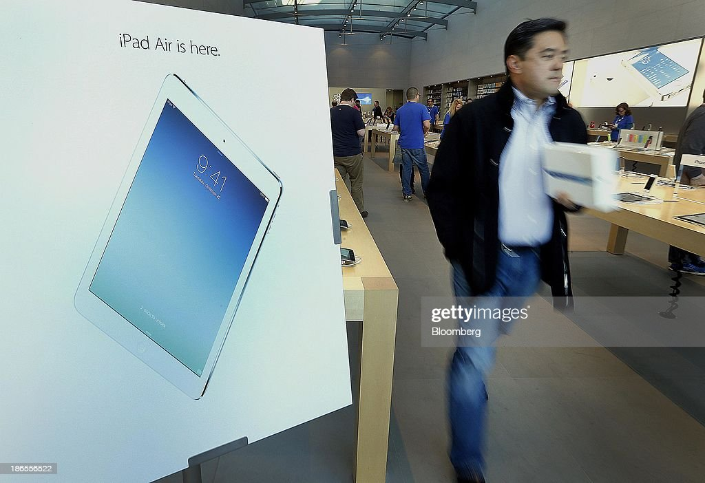 An advertisement for the new Apple Inc. iPad is displayed as a customer exits a store in Palo Alto, California, U.S., on Friday, Nov. 1, 2013. Apple Inc.'s forecast for the slowest holiday sales growth in a half decade reflects how iPhones and iPads aren't providing the growth surges they once did as competition accelerates in the saturated mobile market. Photographer: Tony Avelar/Bloomberg via Getty Images