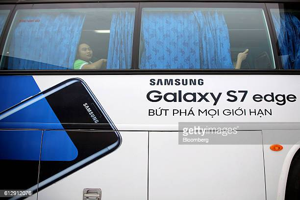 An advertisement for the Samsung Electronics Co Galaxy S7 Edge smartphone is displayed on a company bus transporting workers at the Samsung...