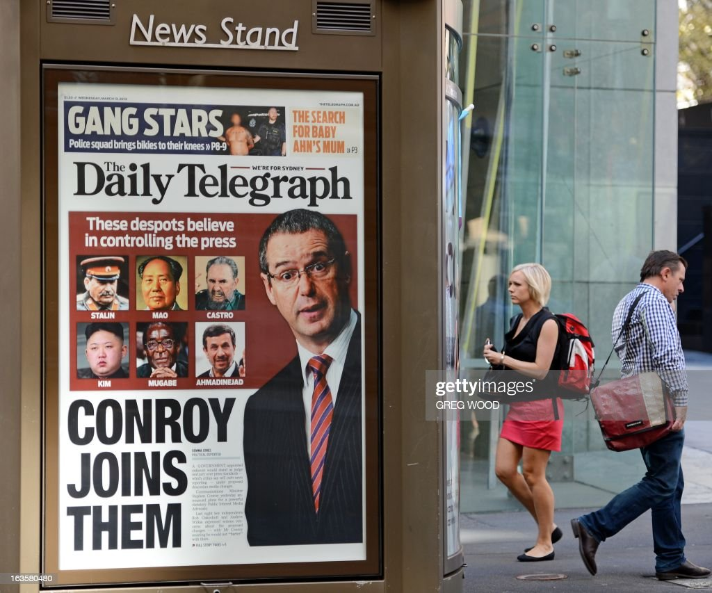 An advertising billboard (L) showing the front page of Sydney's tabloid newspaper the Daily Telegraph is shown in the Sydney central business district on March 13, 2013. The paper likened Australian Communications Minister Stephen Conroy seen at right in the advertisement, to famous despots including Kim Jong-Un and Robert Mugabe, as he was condemned by Rupert Murdoch's local operations after he unveiled proposed media reforms. The proposed changes will include a new public interest test for major mergers and stronger self-regulation requirements for the print media. AFP PHOTO / Greg WOOD