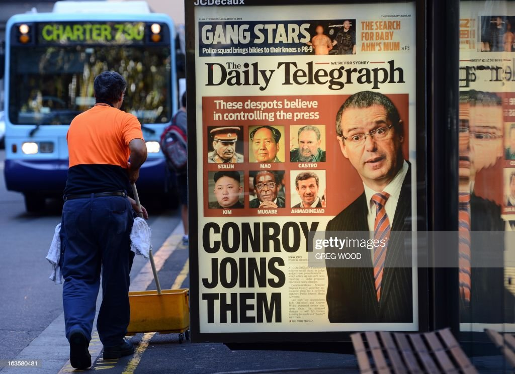 An advertising billboard (C) showing the front page of Sydney's tabloid newspaper the Daily Telegraph is shown in the Sydney central business district on March 13, 2013. The paper likened Australian Communications Minister Stephen Conroy seen at right in the advertisement, to famous despots including Kim Jong-Un and Robert Mugabe, as he was condemned by Rupert Murdoch's local operations after he unveiled proposed media reforms. The proposed changes will include a new public interest test for major mergers and stronger self-regulation requirements for the print media. AFP PHOTO / Greg WOOD