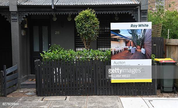 An advertising board for an upcoming auction sits outside a house in Sydney on December 6 2016 as Australia keeps it's official interest rates...