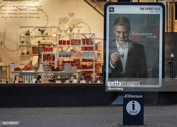 An advertising poster for Nespresso coffee a unit of Nestle SA stands outside an Iittala homeware store operated by Fiskars Oyj in Utrecht...