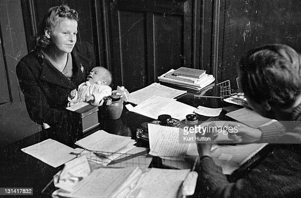 An adviser from the Citizens' Advice Bureau making a home visit to an elderly client 13th February 1943 Original Publication Picture Post 1375...