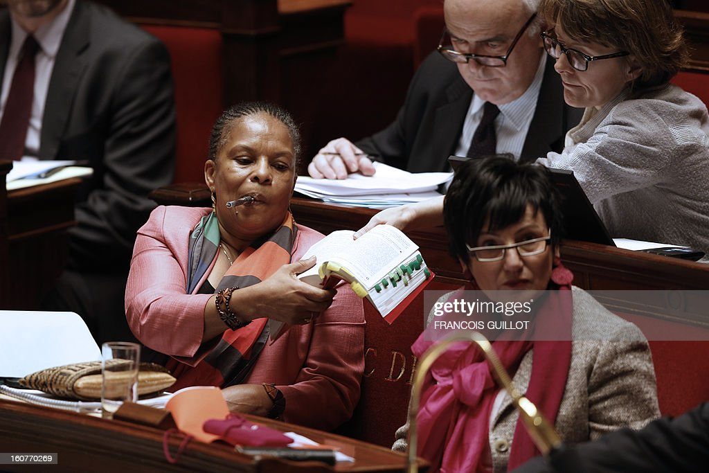 An advisor (R) holds a civil code to French Justice Minister Christiane Taubira (L) during the debate to allow gay couples to get married and adopt children on February 5, 2013 at the National Assembly in Paris. Three days before, members of Parliament voted 249-97 in favour of Article One of the draft law, which redefines marriage as being a contract between two people rather than necessarily between a man and a woman. At right, foreground, Junior Minister for Family Dominique Bertinotti.