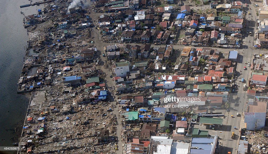 An aerial image taken on board a Japanese C-130 cargo plain shows Tacloban coastal villages on December 8, 2013 in the aftermath of Super Typhoon Haiyan that hit the central Philippines on November 8. A month after one of the strongest typhoons ever recorded hit the Philippines, masses of survivors are living amid rubble in rebuilt shanty homes and experts say reconstructing destroyed communities will take years. AFP PHOTO / Jay DIRECTO