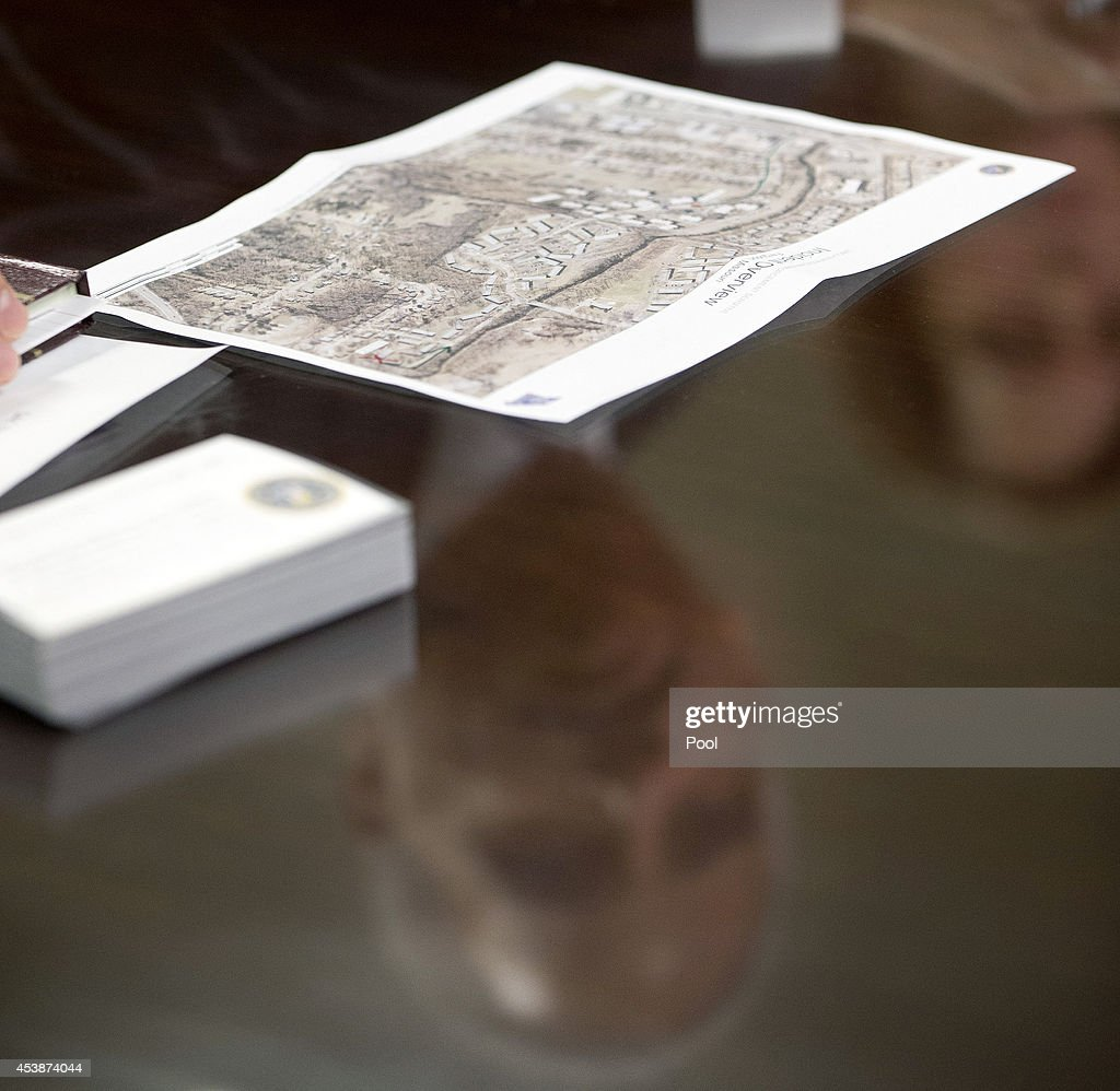 An aerial map of Ferguson, Mo., is seen on the table during Attorney General Eric Holder's meeting at the FBI building August 20, 2014 in St. Louis, Missouri. Holder is traveling to Ferguson, Mo., to oversea the federal government's investigation into the shooting of 18-year-old Michael Brown by a police officer on Aug. 9th. Holder promised a 'fair and thorough' investigation into the fatal shooting of a young blackman, Michael Brown, who was unarmed when a white police officer shot him multiple times.