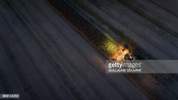 An aerial picture shows a combine harvester during a rape harvest on July 4 2017 near Monthodon central France / AFP PHOTO / GUILLAUME SOUVANT