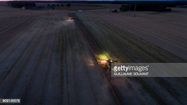 An aerial picture shows combine harvesters in action during a rape harvest on July 04 2017 near Monthodon central France / AFP PHOTO / GUILLAUME...