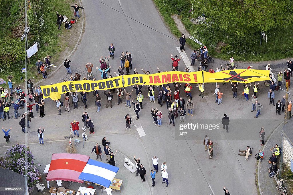An aerial picture shows people gathering to form a human chain as a protest around the site against a project to build an international airport near Notre-Dame-des-Landes on May 11, 2013. The disputed project has been put on hold due to changes requested by several government reports, and will likely be postponed beyond the scheduled opening planned for 2017.
