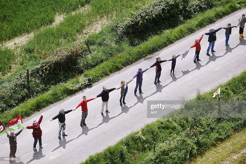 An aerial picture shows people joining hands to form a human chain as a protest around the site against a project to build an international airport near Notre-Dame-des-Landes on May 11, 2013. The disputed project has been put on hold due to changes requested by several government reports, and will likely be postponed beyond the scheduled opening planned for 2017.