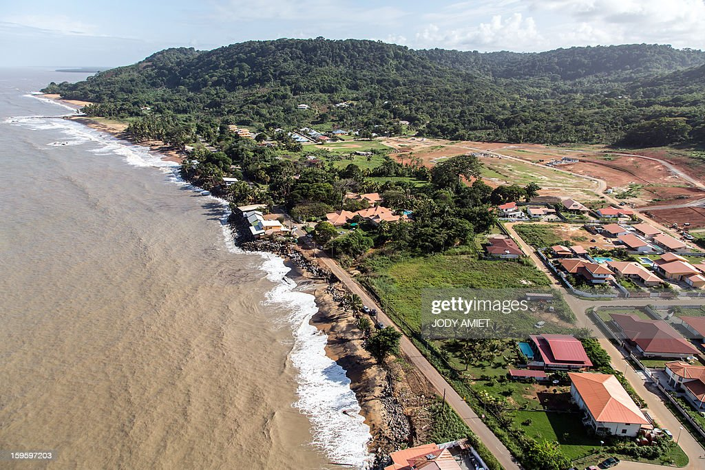 An aerial picture taken on January 15, 2013 shows houses along the ocean in Remire Montjoly, in the French Guiana overseas region. The coast of Guyana and several houses have been 'damaged' due to high tides. In 2001, in this place there was still a 300-400m of beach. AFP PHOTO / JODY AMIET