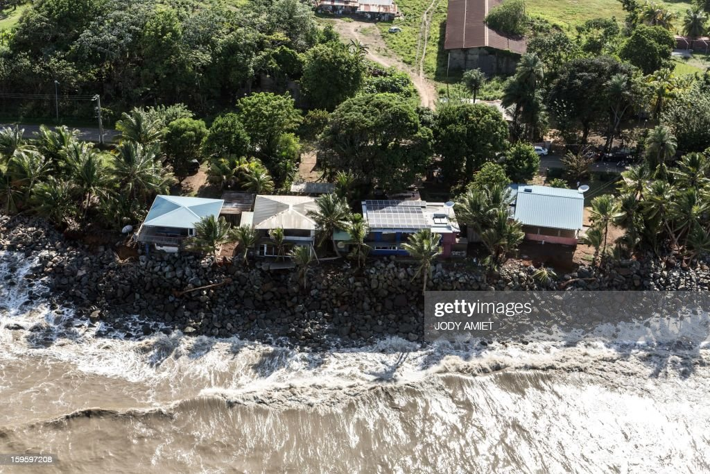 An aerial picture taken on January 15, 2013 shows houses along the ocean in Remire Montjoly, in the French Guiana overseas region. The coast of Guyana and several houses have been 'damaged' due to high tides. Residents had consolidated with rocks around their houses to protect their homes from waves during high tides.