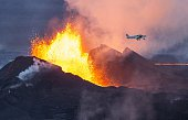 An aerial picture taken on September 14 2014 shows a plane flying over the Bardarbunga volcano spewing lava and smoke in southeast Iceland The...