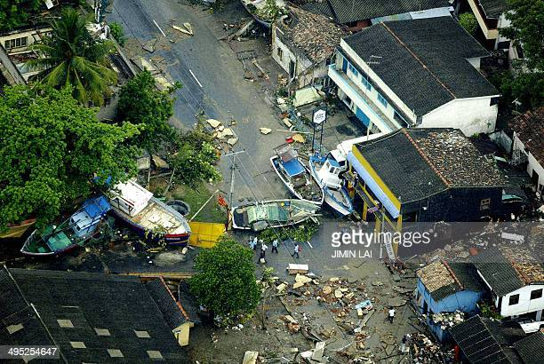 An aerial shot taken from a helicopter shows boats lying on a road after being washed up from the sea by tsunamis in the Galle district in the...