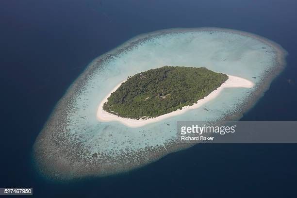 An aerial view of a completely uninhabited deserted island seen from a regional aircraft passing overhead atolls and islands an hour's flying time...