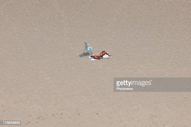 An aerial view of a lone sunbather on De Panne beach taken from a helicopter on July 17 2013 in Belgium
