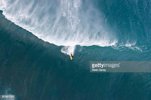 An aerial view of a young man body boarding on a huge wave at Pipeline on the North Shore of Oahu, H