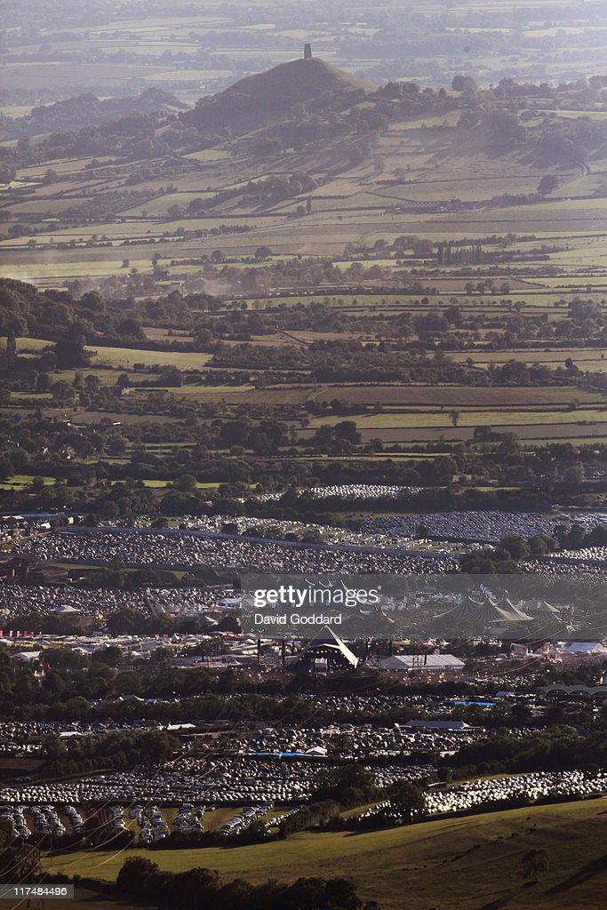 An aerial view of Glastonbury Tor rising behind the Glastonbury Festival site at Worthy Farm in Pilton on June 26, 2011 in Glastonbury, England. The festival, which started in 1970 when several hundred hippies paid 1 GBP to attend, has grown into Europe's largest music festival attracting more than 175,000 people over five days.