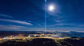 View of Hobart, Tasmania from Mt. Wellington with the Spectra light display. Spectra is a light and sound artwork installed in front of the Cenotaph that sits atop a small rise on the western shore of