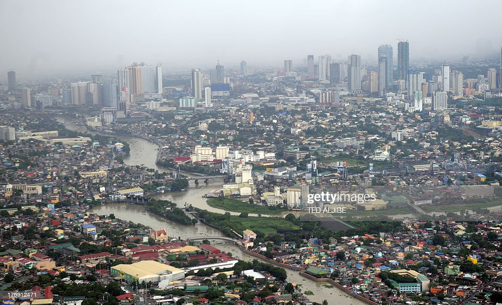 An aerial view of inundated rivers after heavy rains overnight flooded streets in Manila on August 19, 2013. Torrential rain paralysed large parts of the Philippine capital August 19, as neck-deep water swept through homes, while floods in northern farming areas claimed at least one life. AFP PHOTO/TED ALJIBE