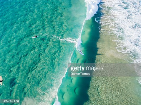 An aerial view of surfers waiting on the surfboard for a wave at the beach : Stock Photo