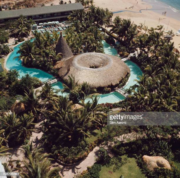 An aerial view of the beachside grounds of the Hilton Hotel in Acapulco Mexico with its swimming pool and thatched pool bar and restaurant February...
