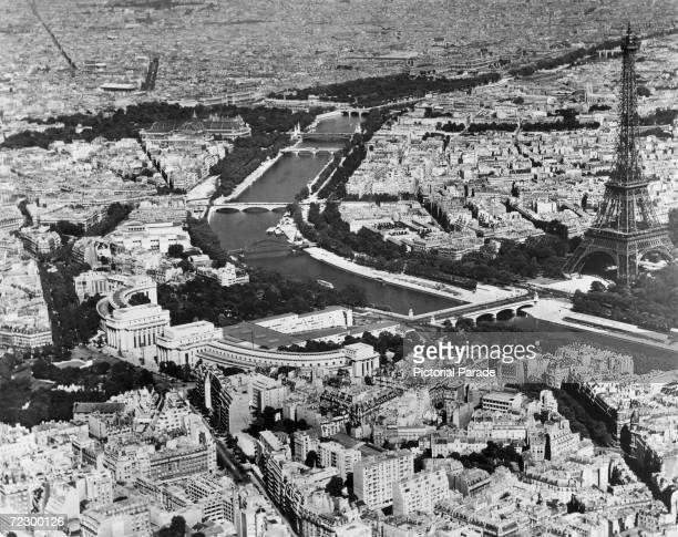 An aerial view of the river Seine running through the city of Paris the Eiffel Tower is on the right circa 1955