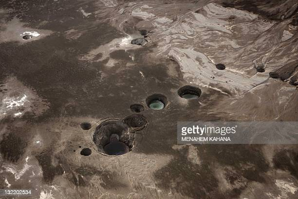 An aerial view photo shows sinkholes created by the drying of the Dead Sea near Kibbutz Ein Gedi on November 10 2011 The Dead Sea is one of the sites...