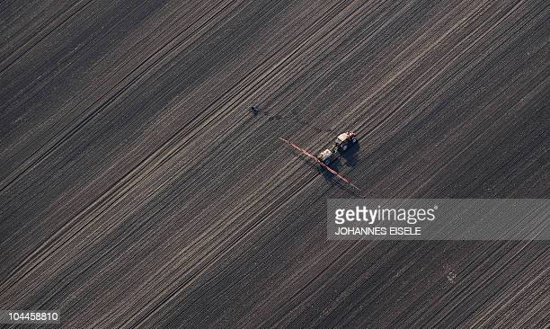 An aerial view shows a farmer ploughing a field on September 22 2010 near Heist north of Hamburg northern Germany AFP PHOTO / JOHANNES EISELE