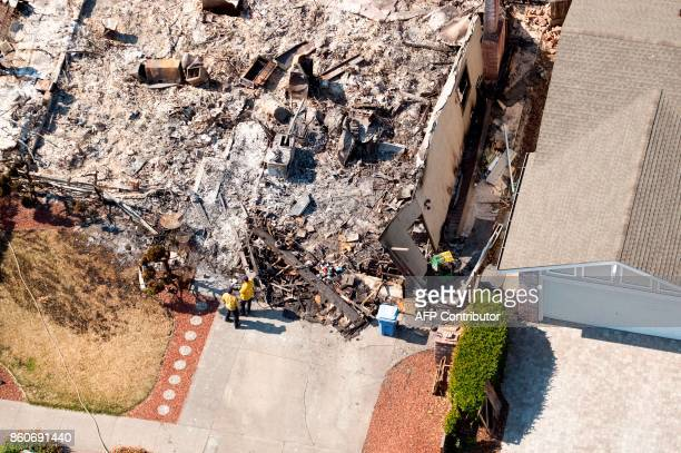 An aerial view shows firefighters working at a burned property in Santa Rosa California on October 12 2017 Hundreds of people are still missing in...