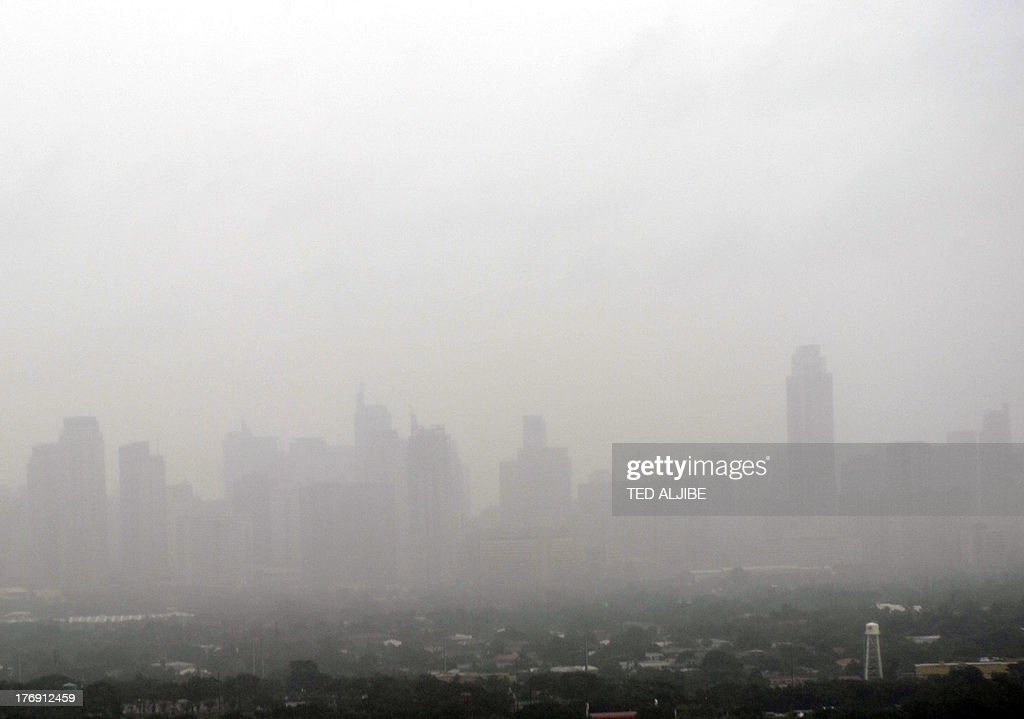 An aerial view shows heavy mist engulfing buildings near the financial district of Manila as heavy rains flooded streets on August 19, 2013. Torrential rain paralysed large parts of the Philippine capital August 19, as neck-deep water swept through homes, while floods in northern farming areas claimed at least one life.