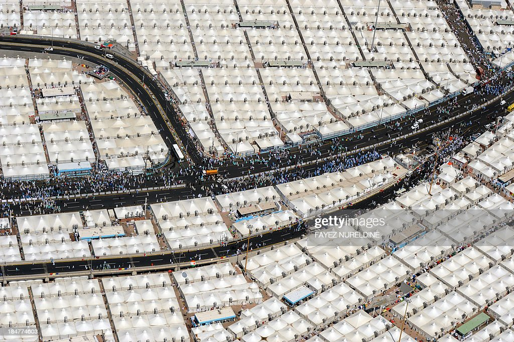 An aerial view shows Muslim pilgrims walking past tents as they make their way to the area where they throw pebbles at pillars during the 2nd day of 'Jamarat' ritual, the stoning of Satan, in Mina near the holy city of Mecca, on October 16, 2013. Pilgrims pelt pillars symbolising the devil with pebbles to show their defiance on the third day of the hajj as Muslims worldwide mark the Eid al-Adha or the Feast of the Sacrifice, marking the end of the hajj pilgrimage to Mecca and commemorating Abraham's willingness to sacrifice his son Ismail on God's command in the holy City of Mecca.