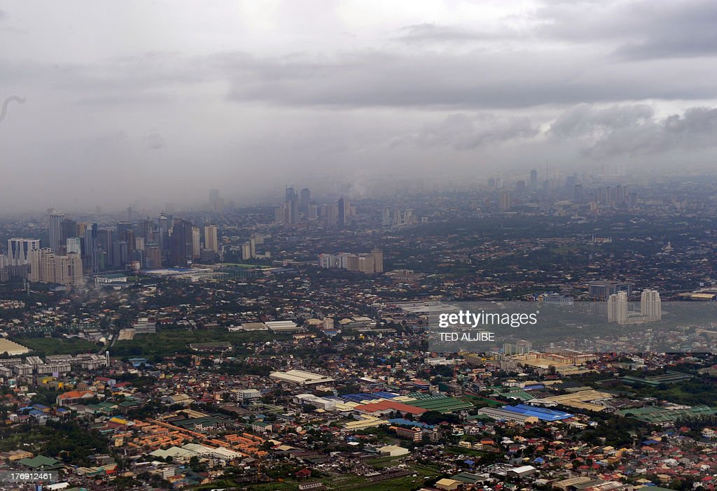 An aerial view shows rain clouds over buildings near the financial district of Manila as heavy rains flooded streets on August 19, 2013. Torrential rain paralysed large parts of the Philippine capital August 19, as neck-deep water swept through homes, while floods in northern farming areas claimed at least one life.