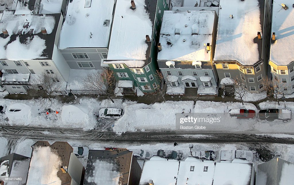 An aerial view shows that cars are still packed in by show on the streets of South Boston as dusk approaches on Sunday, Feb. 10, 2013, after a blizzard hit New England.