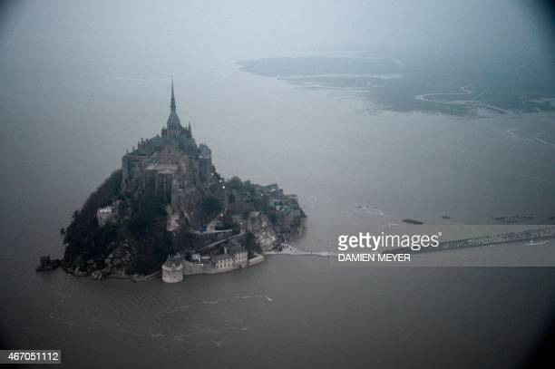 An aerial view shows the MontSaintMichel surrounded by the sea during high tide on March 20 2015 A 'supertide' is expected on March 21 2015 to affect...