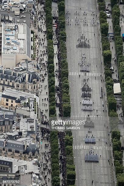 An aerial view taken from a helicopter shows the annual Bastille Day military parade on the ChampsElysees avenue in Paris on July 14 2016 France...