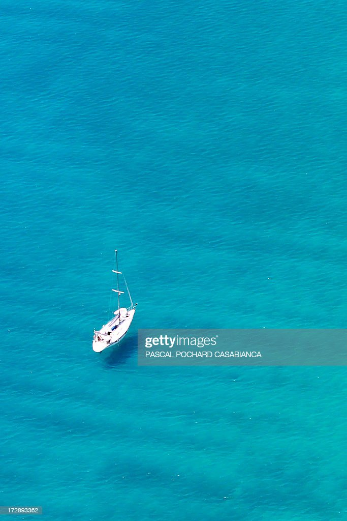 An aerial view taken on July 1, 2013, shows a sailing-boat sailing off Cargese on the coast of the French Mediterranean Island of Corsica. AFP PHOTO / PASCAL POCHARD-CASABIANCA