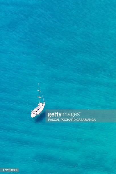 An aerial view taken on July 1 shows a sailingboat sailing off Cargese on the coast of the French Mediterranean Island of Corsica AFP PHOTO / PASCAL...