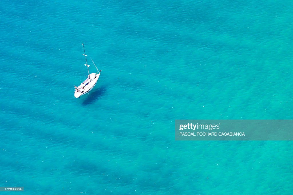 An aerial view taken on July 1, 2013, shows a sailing-boat sailing off Cargese on the coast of the French Mediterranean Island of Corsica.